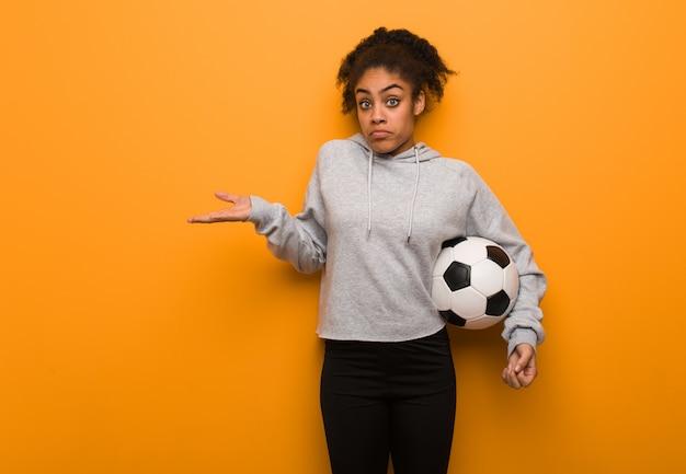 Mulher negra nova da aptidão que duvida e que shrugging ombros. segurando uma bola de futebol.