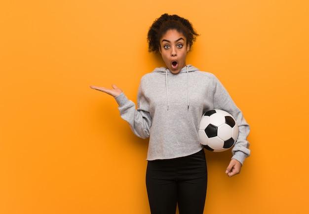 Mulher negra nova da aptidão que guarda algo na mão da palma. segurando uma bola de futebol.