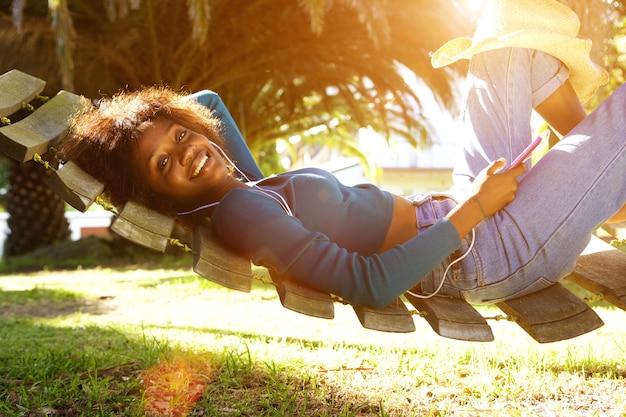 Mulher negra nova de sorriso que escuta a música com telefone esperto