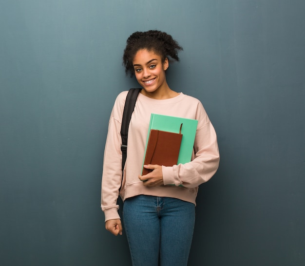 Mulher negra nova do estudante alegre com um sorriso grande. ela está segurando livros.