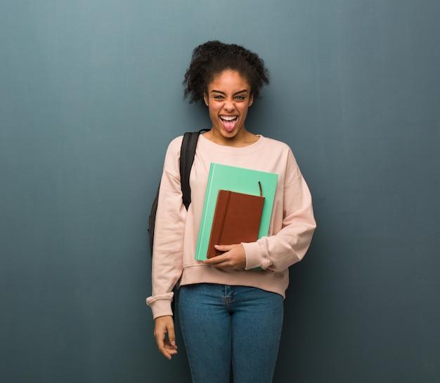 Mulher negra nova do estudante funnny e língua mostrando amigável. ela está segurando livros.