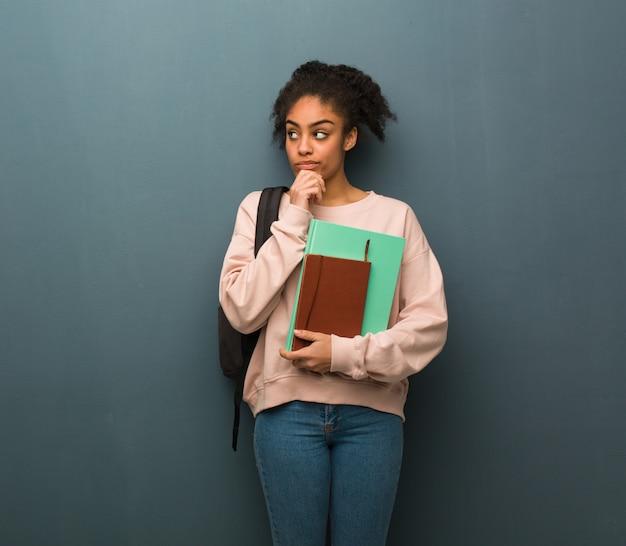 Mulher negra nova do estudante que duvida e confusa. ela está segurando livros.
