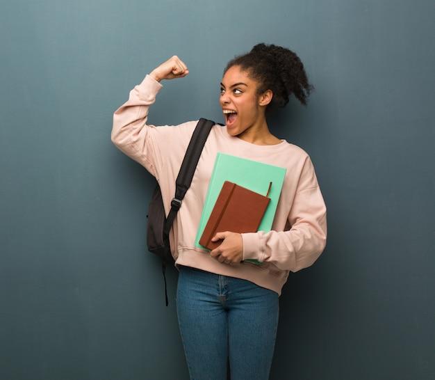 Mulher negra nova do estudante que não se rende. ela está segurando livros.