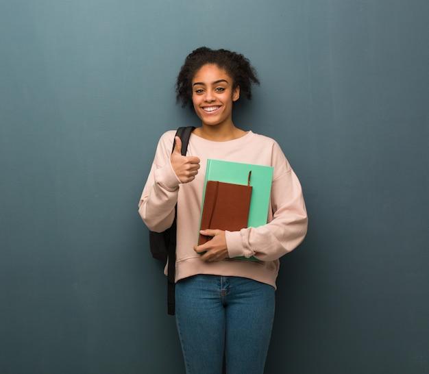 Mulher negra nova do estudante que sorri e que levanta o polegar acima. ela está segurando livros.