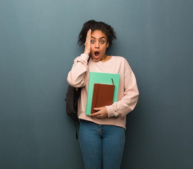 Mulher negra nova do estudante surpreendida e chocada. ela está segurando livros.