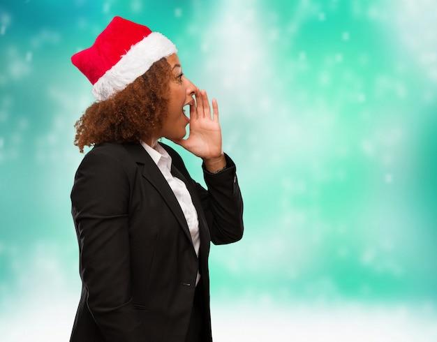 Mulher negra nova do negócio que veste um chapéu do papai noel do chirstmas que sussurra o undertone da bisbolhetice
