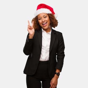 Mulher negra nova do negócio que veste um divertimento do chapéu do papai noel dos chirstmas e feliz fazendo um gesto da vitória