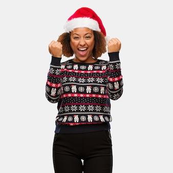 Mulher negra nova em uma camisola de natal na moda com impressão surpreso e chocado