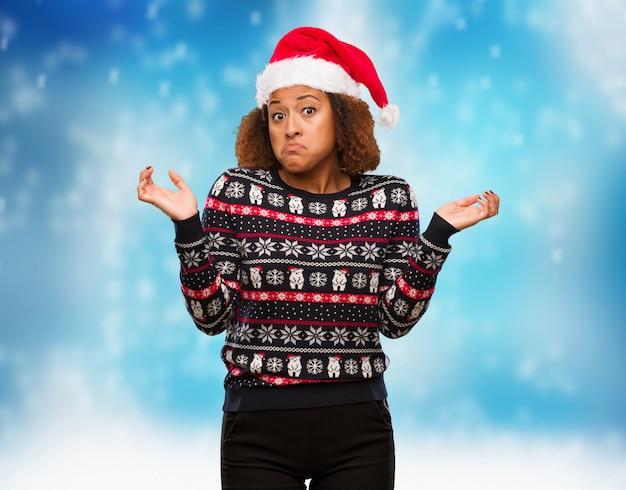 Mulher negra nova em uma camisola na moda do natal com cópia que duvida e que encolhe ombros