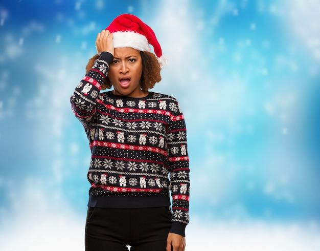 Mulher negra nova em uma camisola na moda do natal com impressão cansado e muito sonolento