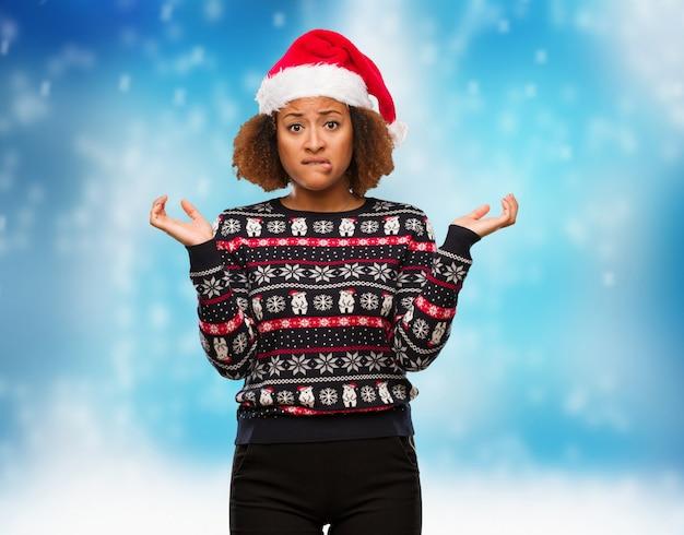 Mulher negra nova em uma camisola na moda do natal com impressão confuso e duvidoso