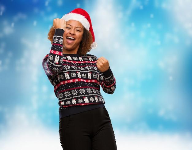 Mulher negra nova em uma camisola na moda do natal com impressão que não se rende
