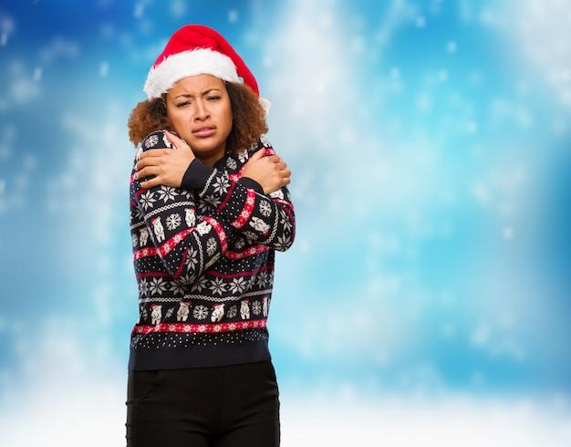 Mulher negra nova em uma camisola na moda do natal com impressão vai frio devido a baixa temperatura