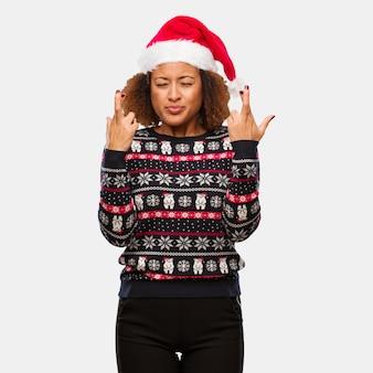 Mulher negra nova em uma camisola na moda do natal com os dedos do cruzamento da cópia para ter a sorte