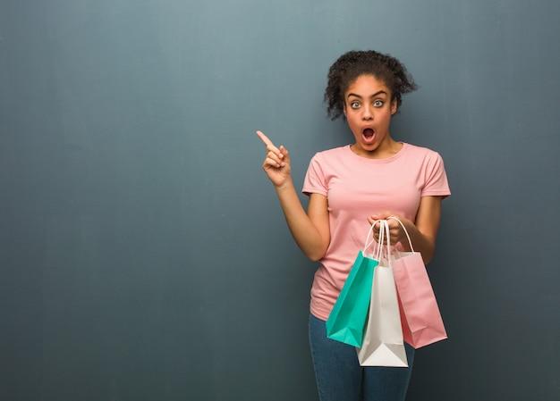 Mulher negra nova que aponta ao lado. ela está segurando uma sacola de compras.
