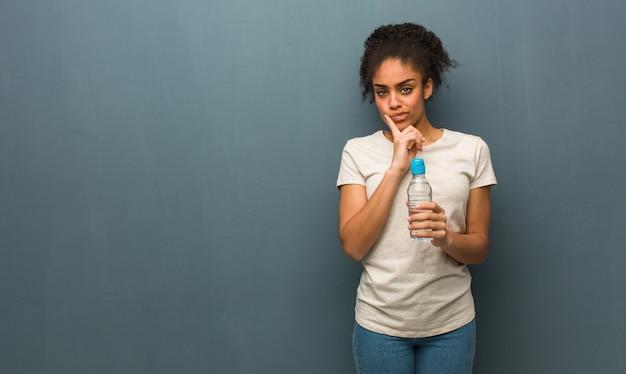 Mulher negra nova que duvida e confusa. ela está segurando uma garrafa de água.