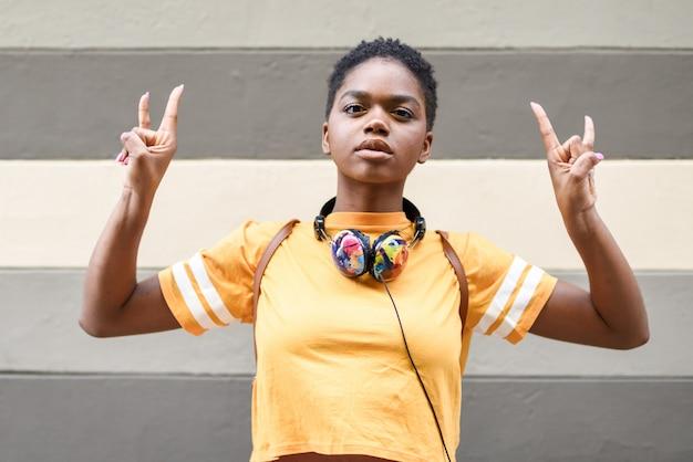 Mulher negra nova que faz o gesto dos chifres com suas mãos ao ar livre.