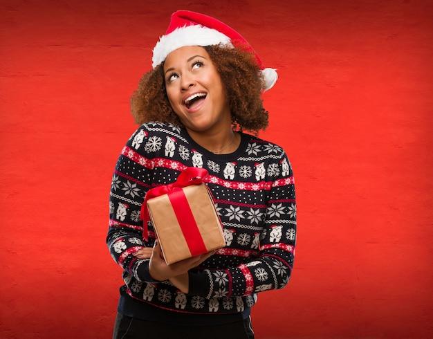 Mulher negra nova que guarda um presente no dia de natal que sonha de conseguir objetivos e finalidades