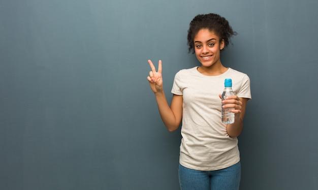 Mulher negra nova que mostra o número dois. ela está segurando uma garrafa de água.