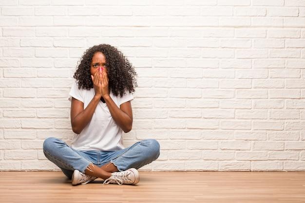 Mulher negra nova que senta-se em um assoalho de madeira muito scared e receoso, desesperado para algo