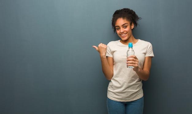 Mulher negra nova que sorri e que aponta ao lado. ela está segurando uma garrafa de água.