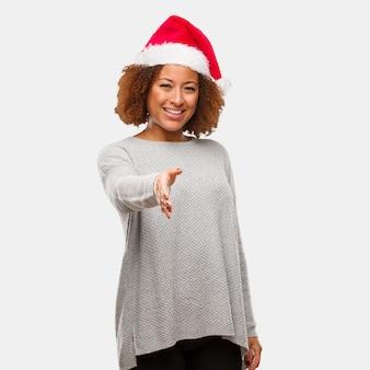Mulher negra nova que veste um chapéu de santa que alcança para fora para cumprimentar alguém