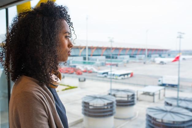 Mulher negra, olhando através da janela do aeroporto de calha