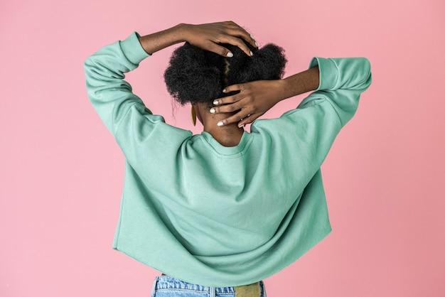 Mulher negra olhando para a parede rosa