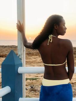 Mulher negra, olhando para longe do pôr do sol na praia