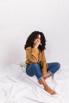 Mulher negra pensativa com flores no bolso da calça jeans