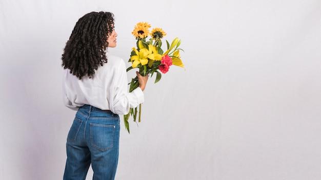 Mulher negra pensativa, segurando o buquê de flores
