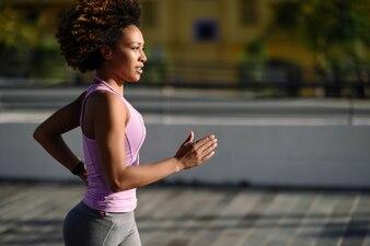 Mulher negra, penteado afro, correndo ao ar livre na estrada urbana.