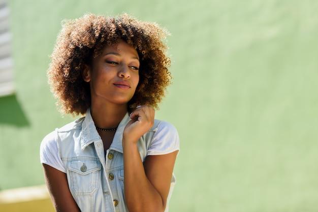 Mulher negra, penteado afro, vestindo roupas casuais em fundo urbano