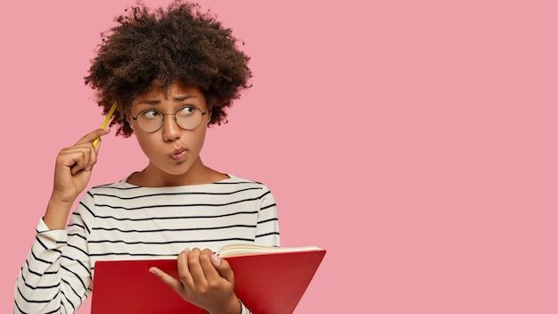 Mulher negra perplexa tem expressão contemplativa, escreve para fazer lista de metas, segura caderno, coça a cabeça com lápis