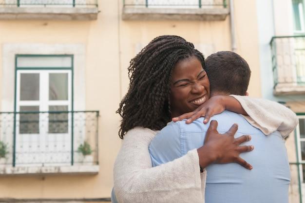 Mulher negra positiva abraçando o namorado ao ar livre