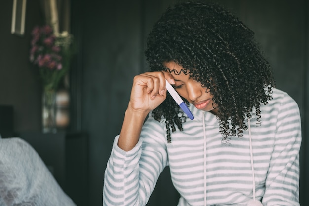 Mulher negra preocupada e triste pensativa com teste de gravidez na cama