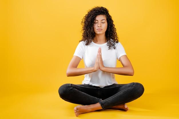 Mulher negra relaxada, meditando em pose de ioga isolada sobre amarelo