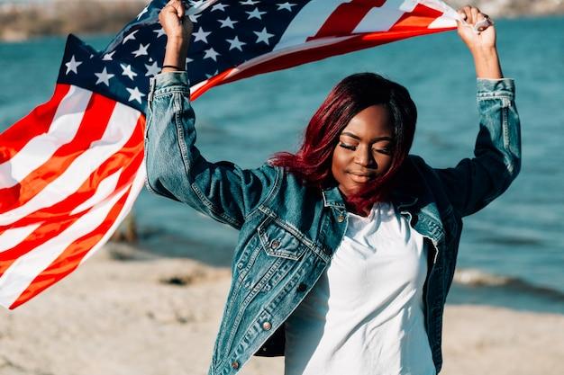 Mulher negra, segurando, bandeira americana, sobre, cabeça, olhos fechando