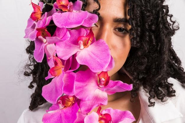 Mulher negra, segurando, flor, em, rosto