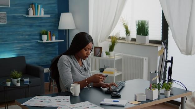 Mulher negra segurando um cartão de crédito eletrônico, digitando pagamento on-line no computador