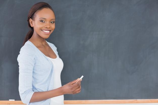 Mulher negra segurando um giz ao lado de um quadro negro