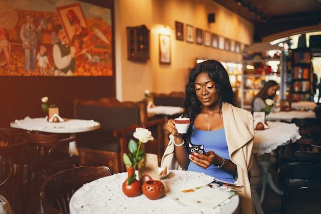 Mulher negra sentada em um café
