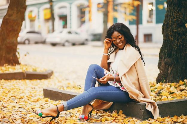 Mulher negra sentada em uma cidade de outono