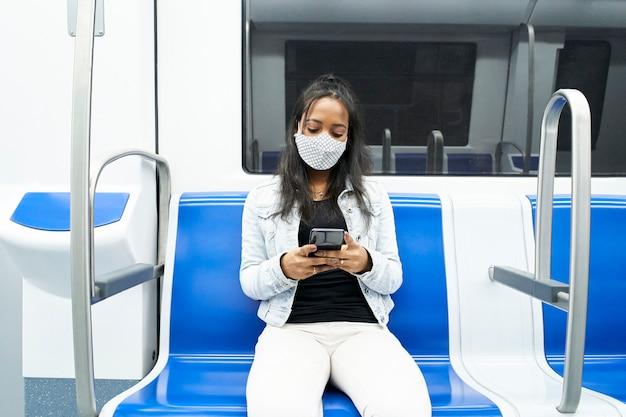 Mulher negra sentada sozinha no vagão do metrô usando um smartphone.