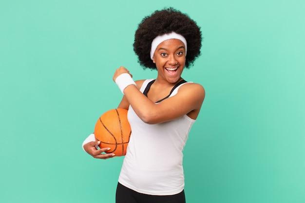 Mulher negra sentindo-se feliz, positiva e bem-sucedida, motivada para enfrentar um desafio ou comemorando bons resultados. conceito de basquete