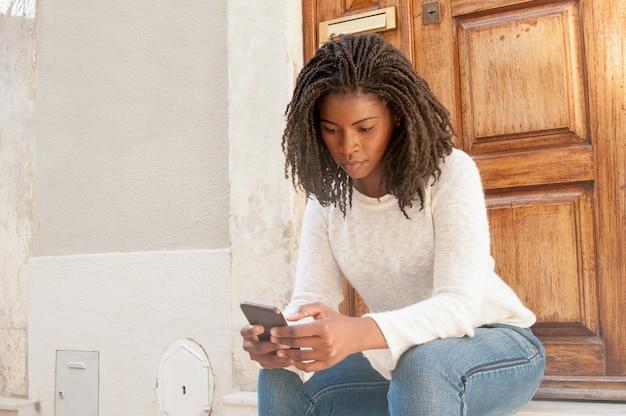 Mulher negra séria que consulta o internet móvel no telefone