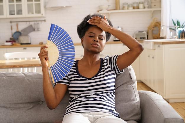 Mulher negra sofrendo de insolação sem ar-condicionado acenando ventilador, deitada no sofá de casa