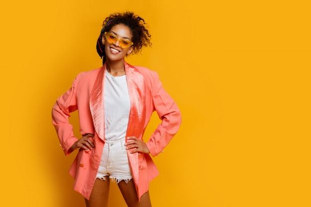Mulher negra sorridente confiante no elegante casaco rosa posando interior sobre fundo amarelo.