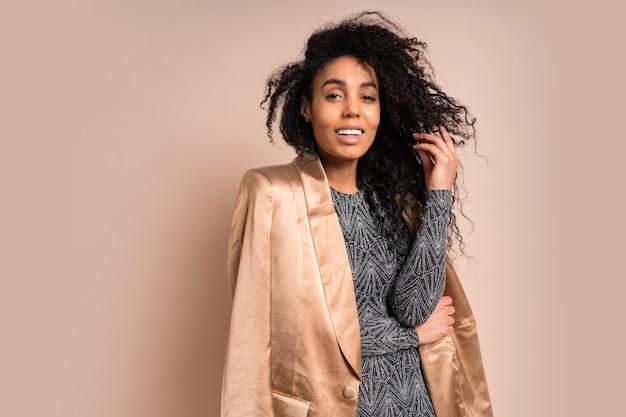 Mulher negra sorridente em jaqueta de seda dourada e vestido brilhante com corpo bronzeado perfeito posando.