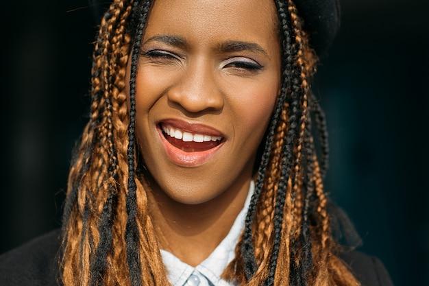 Mulher negra sorridente feliz. humor lúdico. mulher afro-americana sedutora em fundo escuro, corte de cabelo elegante, conceito alegre